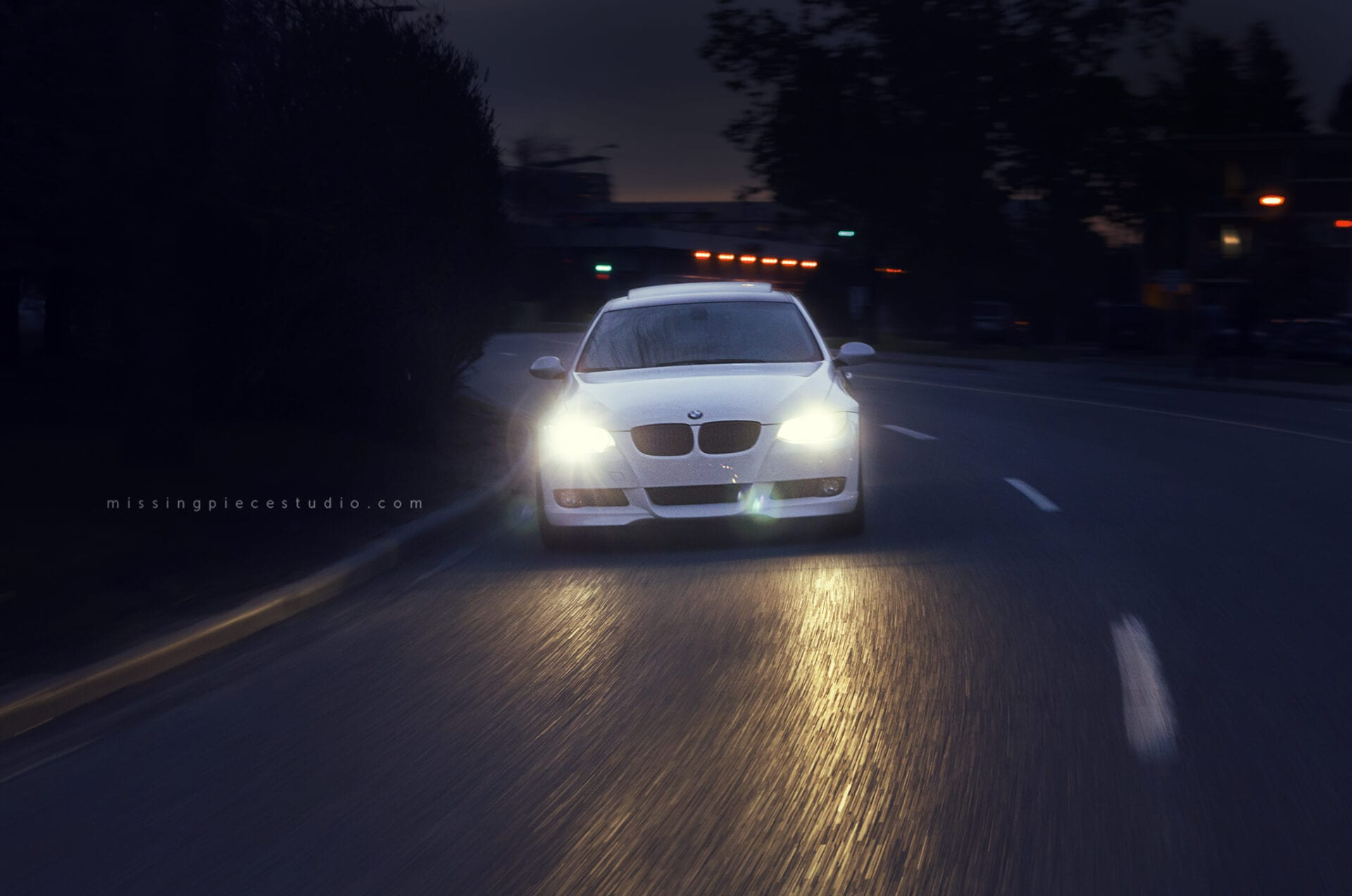 A white BMW 335i going down a curved road