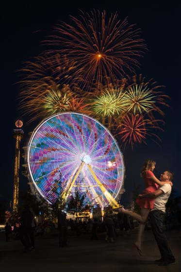 fireworks displaying on top of a ferris wheel while a couple embrace one another