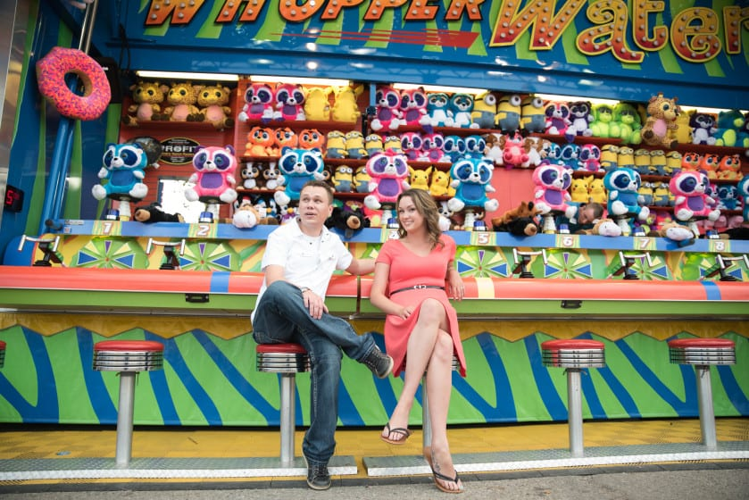 A couple sitting at a carnival game posing for a photo