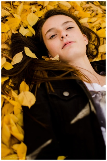 Beautiful girl laying on yellow leaves enjoying the last fall breeze