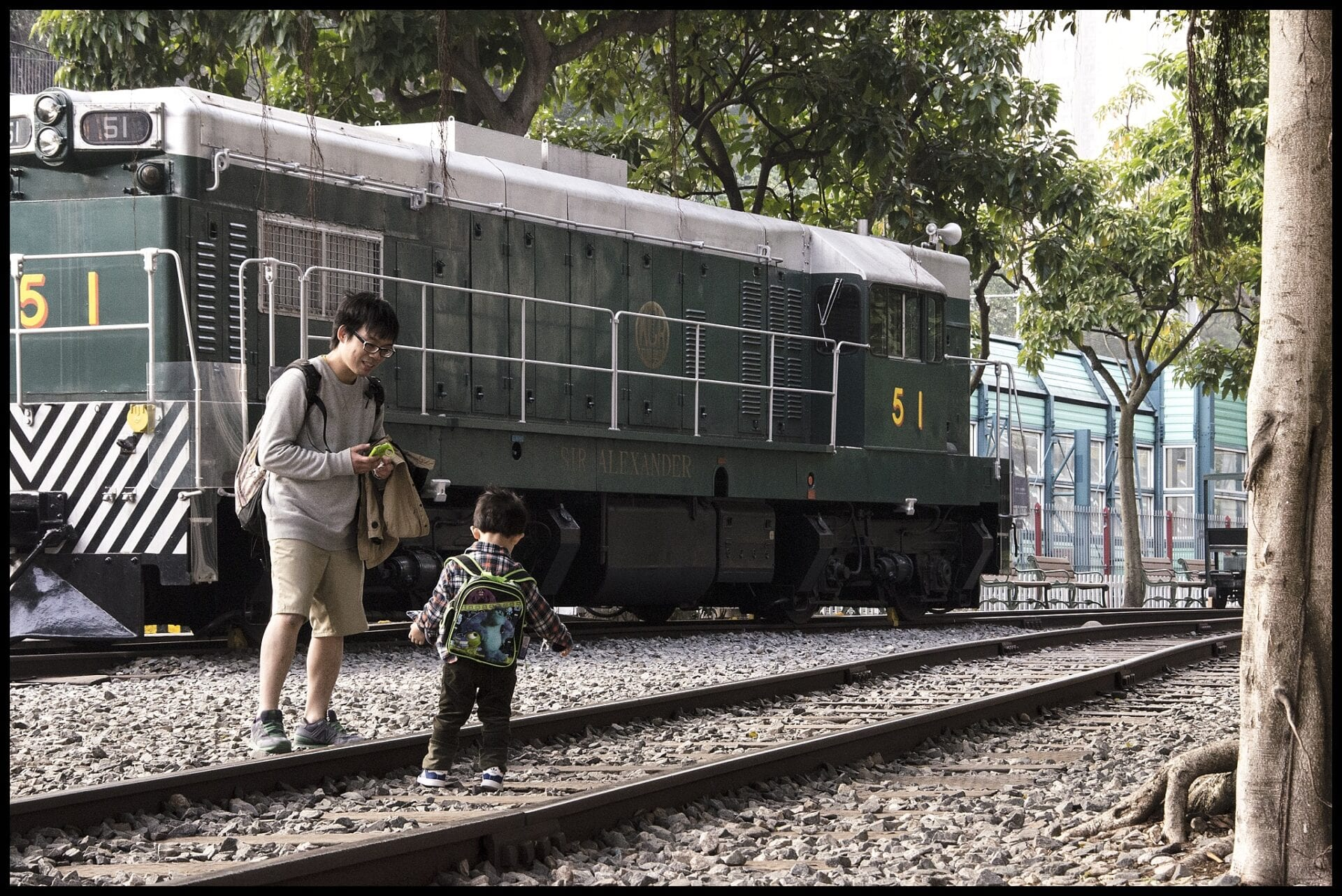 A happy father smiles as his young son walks toward him at the train museum in Hong Kong