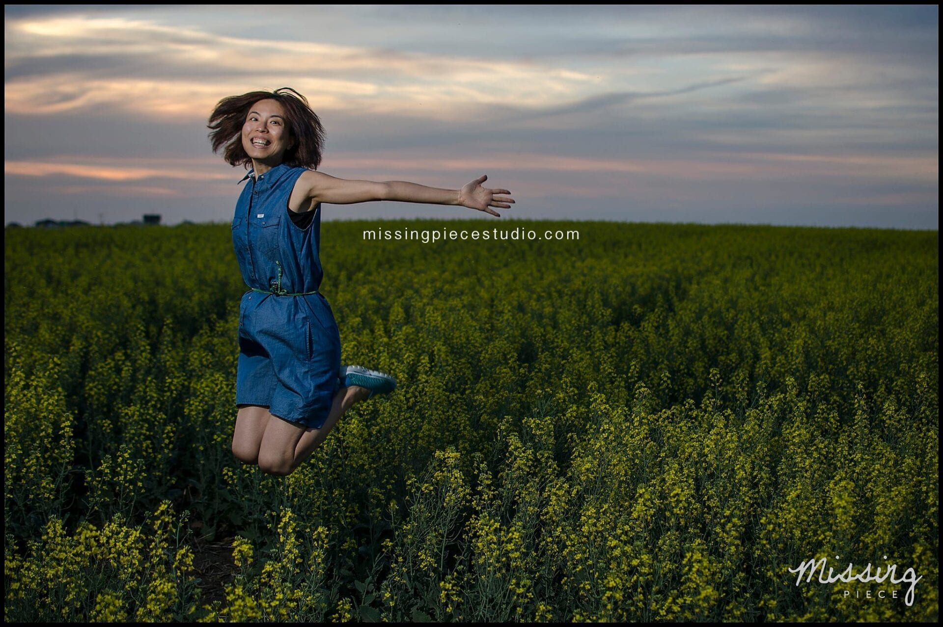 A girl jumping with joy in a beautiful canola field during sunset.